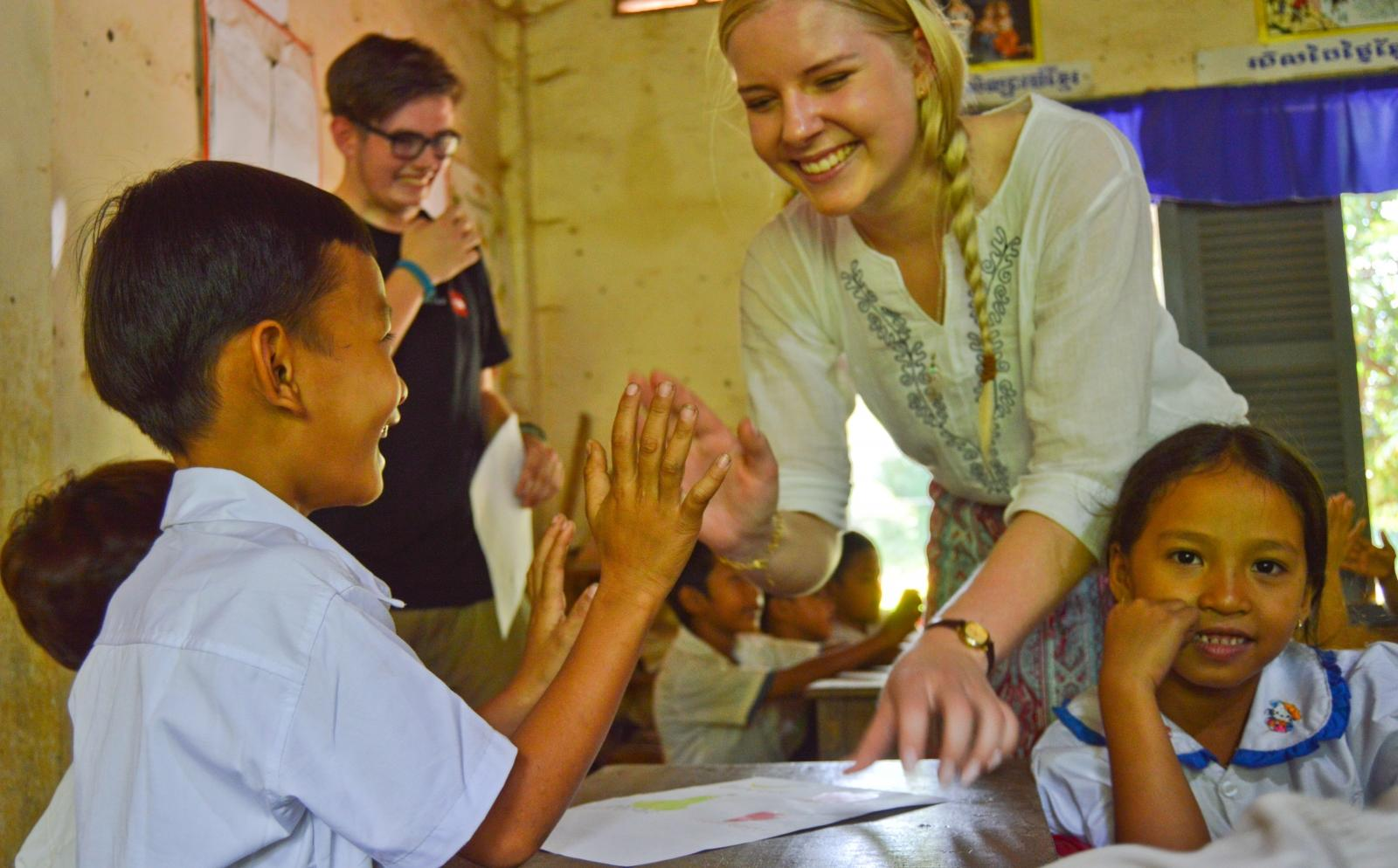 A female volunteer gives a child feedback while teaching abroad after she booked a trip overseas with us.